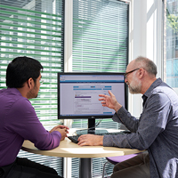 Two individuals talking in front of a computer